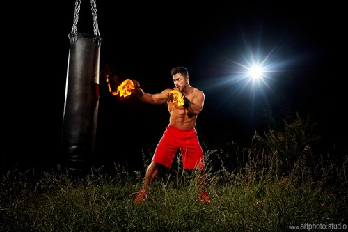 sportsman is training on the black night background,muscular bo